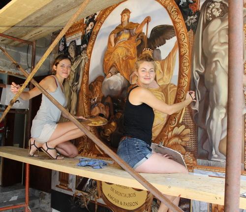 Camille Jadot et Célina Mège à l'ouvrage sur l'échafaudage de la vaste toile dans la grange de la maison Mège à Benivay-Ollon.